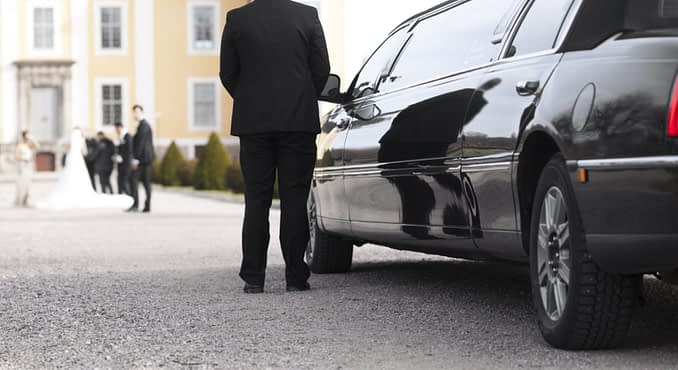 Black limo with driver waiting for bride and groom in front of mansion